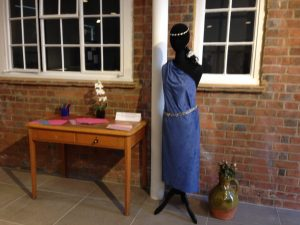 Image of mannequin in blue dress, next to a writing table.