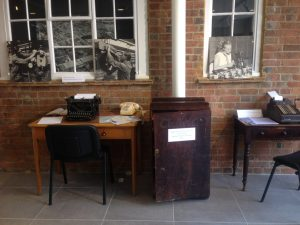 Desks with typewriter and comptometer, with photographs of people working in factories.