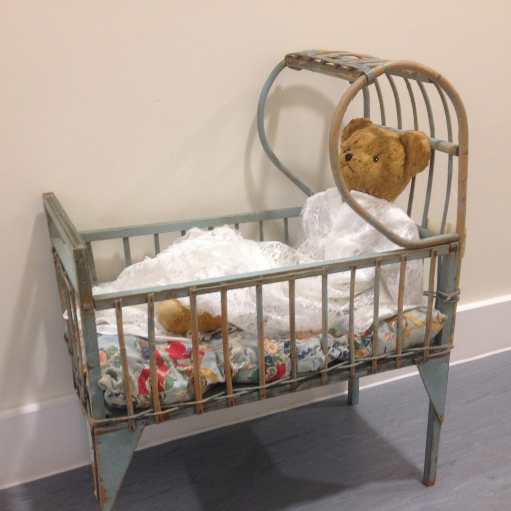 Teddy Bear in doll's cot