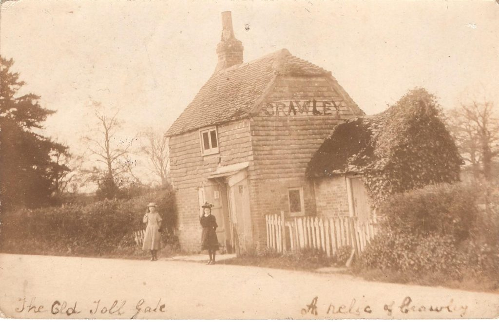 Sepia photograph of Northgate Toll House, with two girls standing outside. The word 'Crawley' appears on the roof of the house. Handwriting at the bottom of the photograph reads 'The Old Toll House. A relic of Crawley.'