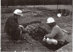two people wearing hardhats, one crouching in a trench in the earth.