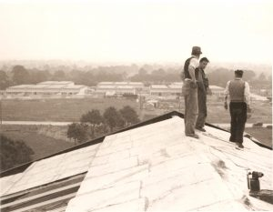 Three workmen standing on the roof of a factory with other factories in the distance