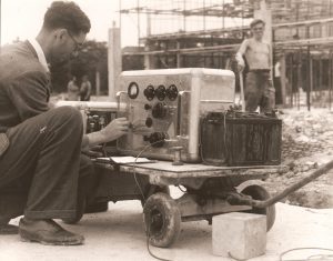 Man on building site turning dials on a machine