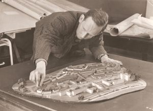Man in suit leaning over a architectural model of housing