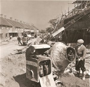 Housing building site. Man operating cement mixer in foreground.