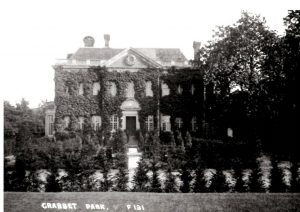 Photograph of Crabbet House, fron view, covered in ivy