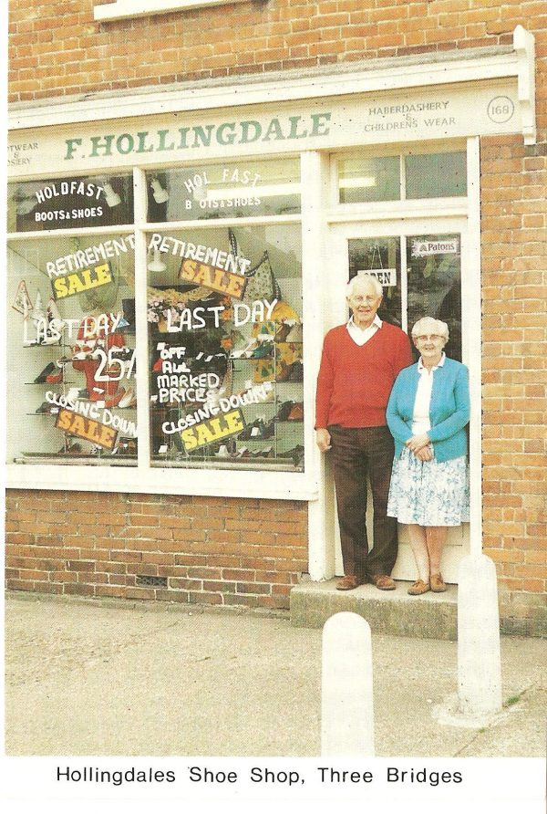Man and woman standing on the steps of a shop. Sign aobve shop window reads 'F.Hollingdale'