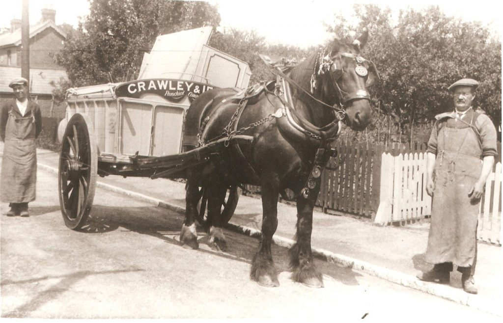 Sepia photograph of horse and cart, with two workmen wearing caps and long aprons.