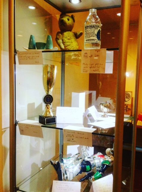 Display cabinet with teddy bear, milk bottle, cruet set, trophy and toy robot, with handwritten labels.