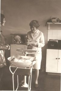 Woman in jacket and skirt weighing a baby