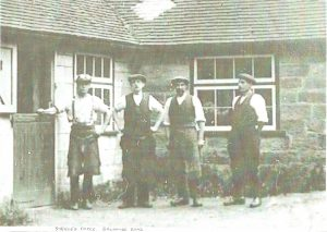 Four men wearing caps standing outside a forge building