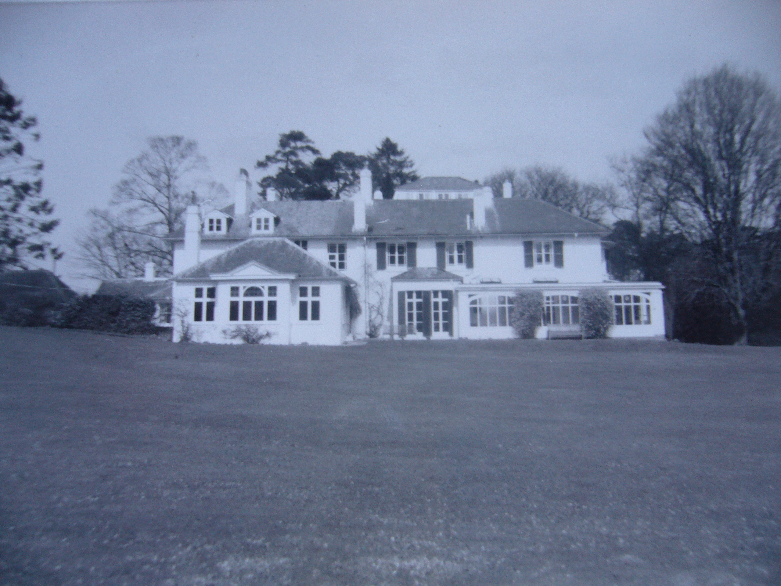 Black and white photograph of the exterior of Broadfield House - large white house with grass in front and trees to the sides and behind.