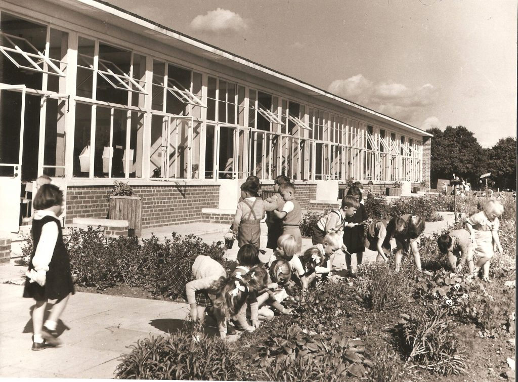 Group of young children weeding a flower bed outside a school classroom.