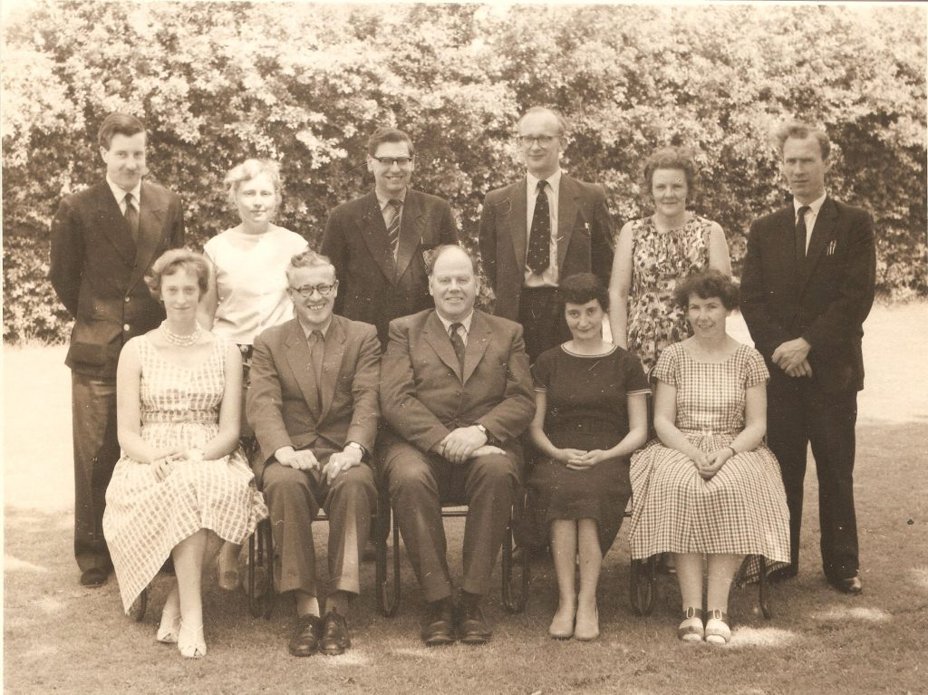 Group photograph of 5 men and 6 women. Five of them are on chairs, 6 are standing behind. The men are wearing suits and the women are in summer dresses.