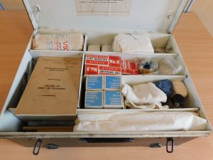 Inside of firt aid box showing contents. Thee include bandages, lint dressing, tape and a booklet entitled 'British Railways Board, British Railways. Record of First Aid Rendered.'