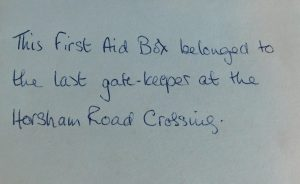 Hand written note that reads 'This First aid Box belonged to the last gate keeper at the Horsham Road Crossing.'
