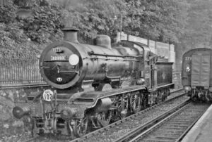 black and white image of locomotive on tracks.
