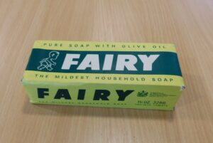 Rectangular cardbaord packagian. Green and yellow. Text reads: Pure soap with olive oil. Fairy. The mildest household soap. The side states the weight to be 11 and a half ounces or 326 grams, and that the box contains two tablets.