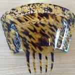 Large tortoiseshell decorative hair comb. Flower design around edge.