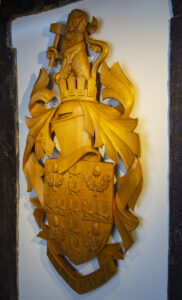 Wooden coat of arms, depicting lion with hammer on top of a crowned helmet. Shield below shows 9 martlets and 4 acorns. Motto reads 'I grow and I rejoice'