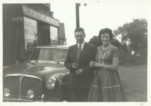 man in suit and woman in polka dot dress standing next to a car. Shop frotnage reading 'Tooting Tyre Service Ltd' is visible in the background.