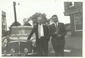 Two men in suits, one leaning on the bonnet of a car
