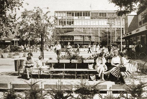 Queens Square. People sitting on benches. Bandstand in the background.