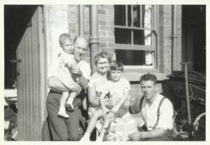 3 adults and 2 children against the outside wall of a building