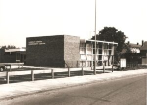 large brick building with writing on side which reads 'Langley Green Community Centre'.