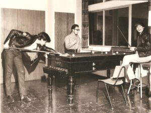 Three young men playing bar billiards. Two are wearing leather jackets.