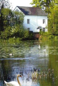 Red boarded Watermill. Mill pond in front with swans.