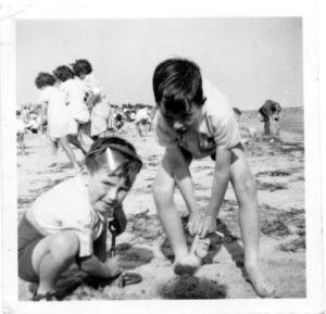 Two young boys digging in the sand on the beach. Both are wearing light coloured shirts and dark shorts.