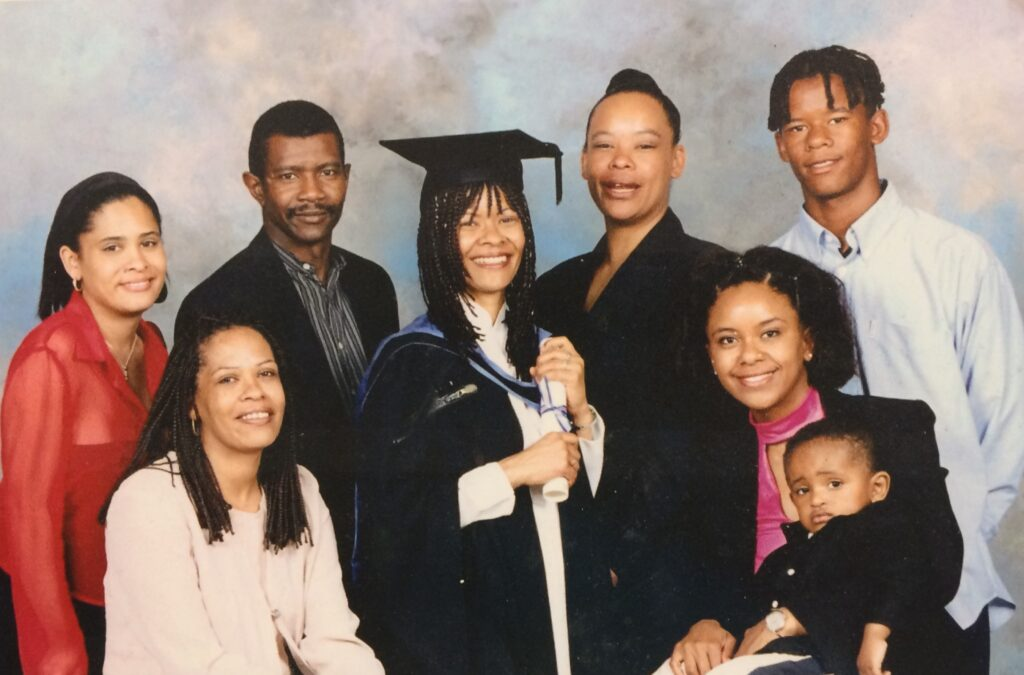 Woman in degree robes and hat holding a certificate, surrounded by six adults. All are smiling. One of the adults has a toddler on her lap.