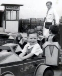 Small child sitting in small car on a fairground roundabout. Man in long white coat with money satchel in background