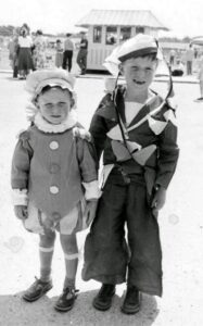 two young children on seafront wearing fancy dress. One is wearing a sailor outfit with a ring of bunting around his head and chest. The other child is wearing a bonnet, doublet and hose.