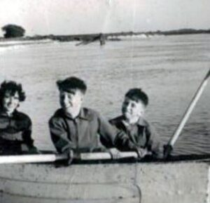 three children in a dinghy. The sea is in the background.