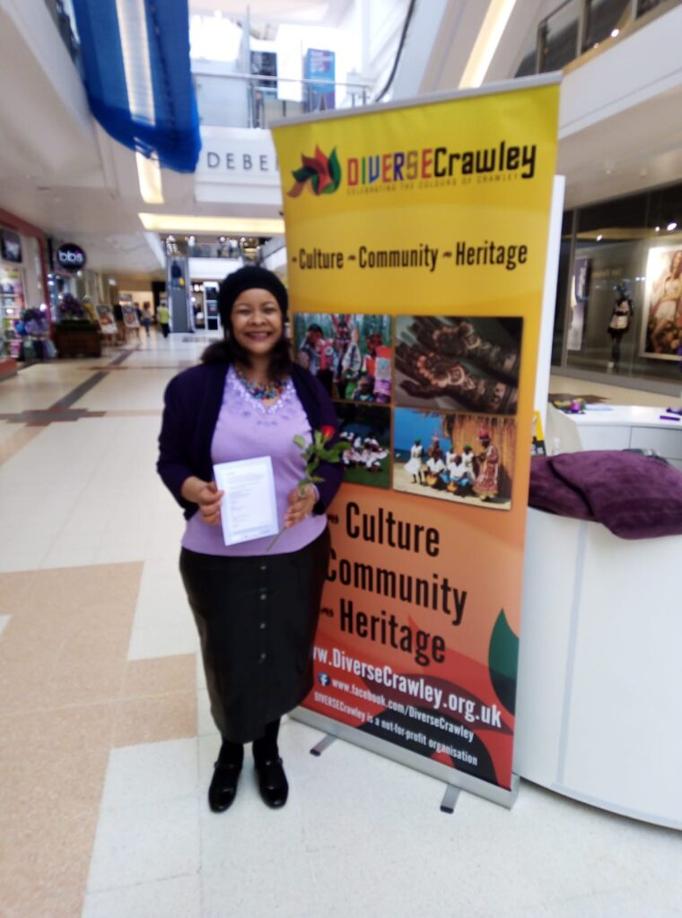 Woman standing next to Diverse Crawley banner in County Mall.