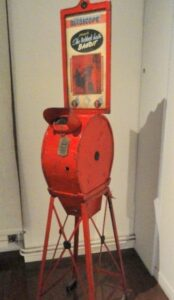 red mutoscope - made of metal, with thin legs and a tapered cylindrical top, with a viewing window and a money slot.