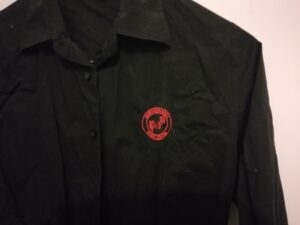 Black shirt with small red logo. Logo has music stave with treble clef, and the words 'Northern Area Music Centre