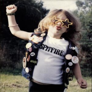 Young child wearing star shaped sunglasses, white t-shirt with word 'Spitfire' on it, and denim waistcoat covered in badges. One arm is raised in the air.