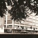 Office building with traffic lights and cars in foreground. Sign on front of building reads 'Starlight Ballroom'.