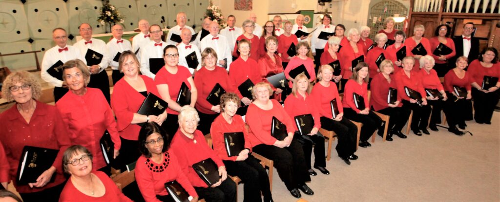 Choir. Women wearing red tops. Men wearing white shirts and red bow ties.