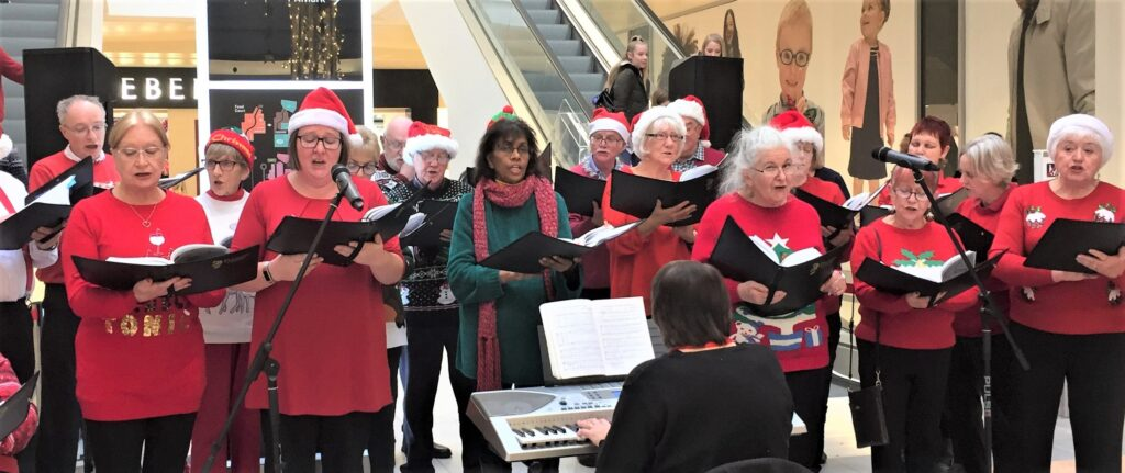 choir dressed in Christmas jumpers singing at the bottom of an escalator.
