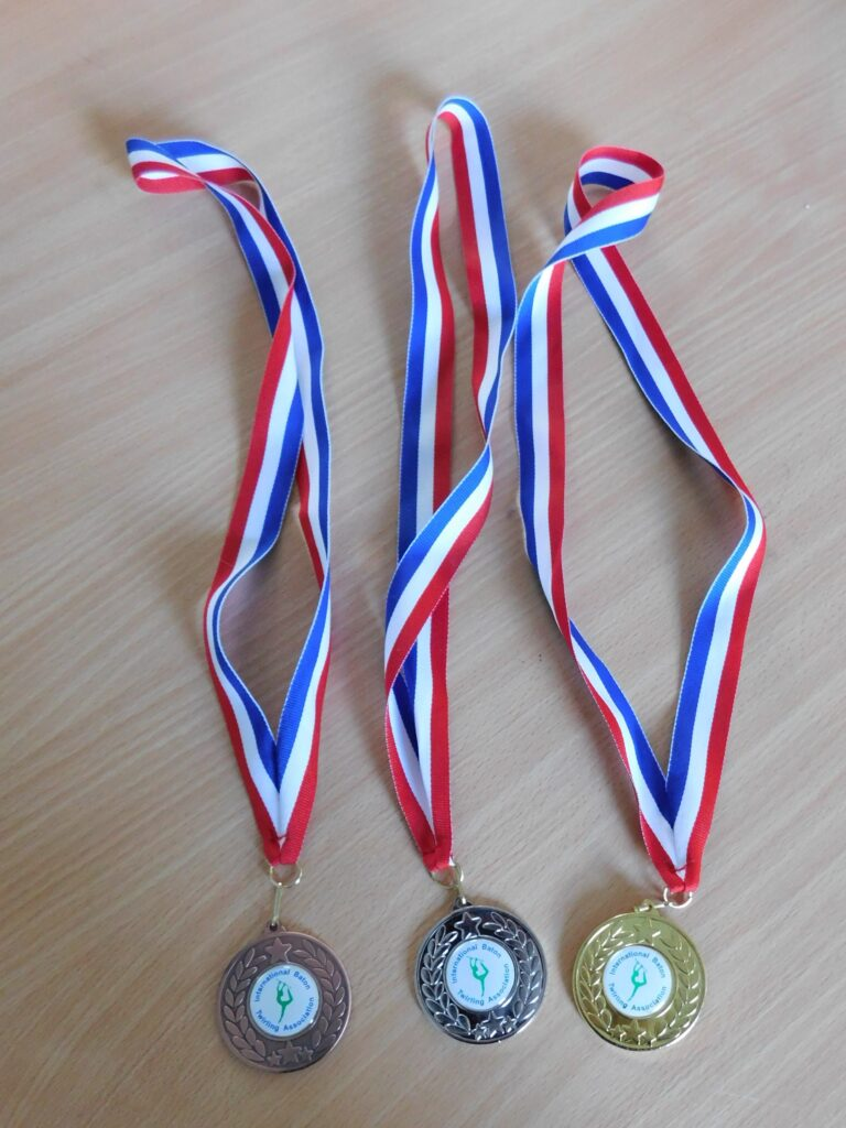 three sports medals on red, white and blue striped ribbons.