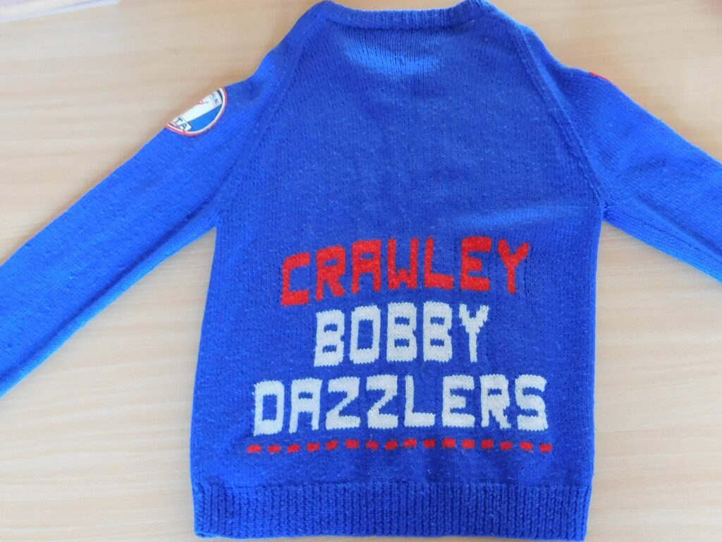 Blue knitted jumper with words 'Crawley Bobby Dazzlers' written on the front.
