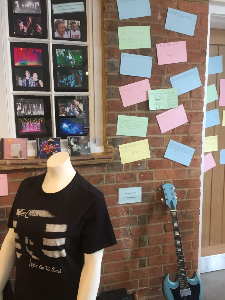 Mannequin torso wearing Cure t-shirt, photographs on wall behind. Index cards on wall behind.