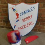 Wooden Shield with painted majorette and words 'Crawley Bobby Dazzlers. Red majorette peaked cap with red, white and blue feathers on the front. Red cap with gold star.