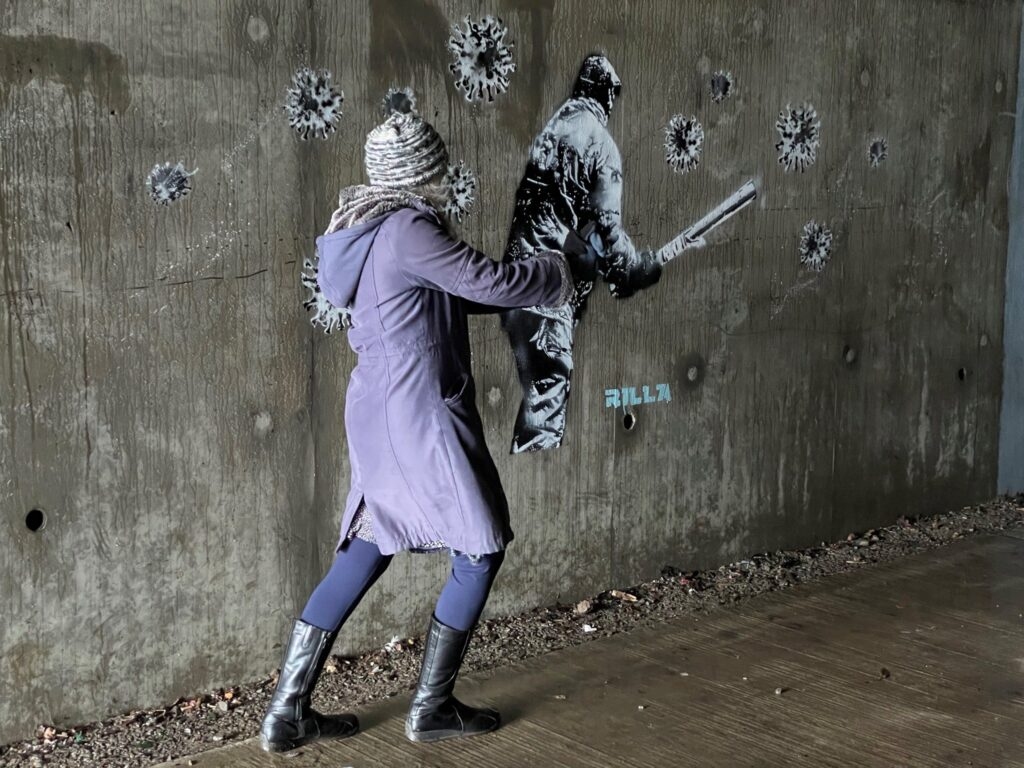Person in purple coat and leggings and grey knitted hat, standing in front of a street painting of a person in coat and trousers holding a stick.